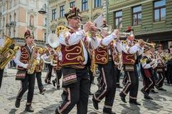 LVIV, ΟΥΚΡΑΝΊΑ - ΤΟ ΜΆΙΟ ΤΟΥ 2018: Μια ορχήστρα πνευστ0ών από χαλκό με τα τύμπανα στα κοστούμια καρναβαλιού περπατά στο κέντρο τη Στοκ Εικόνα