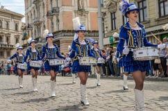 LVIV, ΟΥΚΡΑΝΊΑ - ΤΟ ΜΆΙΟ ΤΟΥ 2018: Χαριτωμένα νέα κορίτσια με τα τύμπανα στα μπλε κοστούμια καρναβαλιού και καπέλα με τα φτερά κα Στοκ Φωτογραφίες