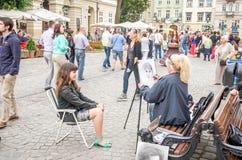 Lviv de Oekraïne Juni 2015: De schilder schildert een portret van het straatmeisje met potlood en document voor foto's Stock Afbeeldingen