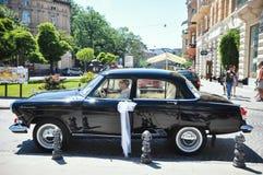 Lviv, de Oekraïne - Juni 5, 2011: Sovjetauto 60 xx jaar Volga gaz-21 De bestuurder denkt het jonge paar in de kerk wordt bekroond Stock Foto's