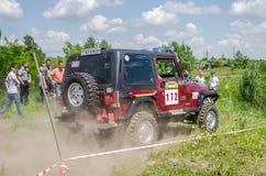 LVIV, DE OEKRAÏNE - MEI 2016: Het reusachtige gestemde drijven van SUV van de autojeep op een landwegverzameling, die een wolk va Stock Fotografie