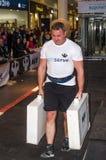 LVIV, DE OEKRAÏNE - NOVEMBER 2016: De sterke strongman atleet draagt zware ijzerkoffers stock afbeeldingen