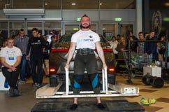 LVIV, DE OEKRAÏNE - NOVEMBER 2016: Sterke atleten strongman liften een zware auto Toyota Corolla stock afbeeldingen
