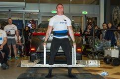 LVIV, DE OEKRAÏNE - NOVEMBER 2016: Sterke atleten strongman liften een zware auto Toyota Corolla royalty-vrije stock fotografie