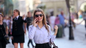 LVIV, DE OEKRAÏNE - OKTOBER 02, 2016: De leuke student in zwarte sunglassesingang in de straat en de bespreking op haar cel telef stock footage