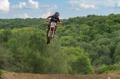 LVIV, DE OEKRA?NE - MAG, 2019: De atletenmotorracer berijdt en springt op een enduromotorfiets op een motocrossspoor stock fotografie