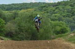 LVIV, DE OEKRA?NE - MAG, 2019: De atletenmotorracer berijdt en springt op een enduromotorfiets op een motocrossspoor royalty-vrije stock foto