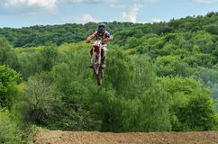 LVIV, DE OEKRA?NE - MAG, 2019: De atletenmotorracer berijdt en springt op een enduromotorfiets op een motocrossspoor stock afbeelding