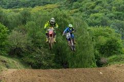 LVIV, DE OEKRA?NE - MAG, 2019: De atletenmotorracer berijdt en springt op een enduromotorfiets op een motocrossspoor stock afbeeldingen