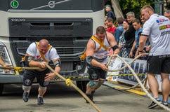 LVIV, DE OEKRAÏNE - JULI 2016: Twee het sterke atletenbodybuilder strongman trekken met kabels twee reusachtige vrachtwagen voor  Royalty-vrije Stock Foto
