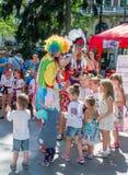Lviv, de Oekraïne - Juli 2015: Yarychstraat Fest 2015 De clown en het Indische spel, zingen en dansen met de kinderen in het park Stock Foto