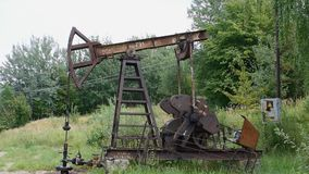 Oil pump in operation in the forest area stock video footage