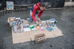 Lviv, Ucrânia - 21 de janeiro de 2018: Mostra para a audiência no meio da rua, assento bonito novo da pintura à pistola nos joelh Foto de Stock
