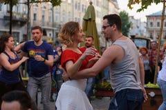 Lviv, Ucrânia - 9 de junho de 2018: Dançarinos da salsa no café exterior perto da fonte de Diana no mercado em Lviv Imagens de Stock