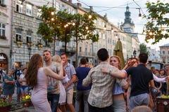 Lviv, Ucrânia - 9 de junho de 2018: Dançarinos da salsa no café exterior perto da fonte de Diana no mercado em Lviv Imagem de Stock
