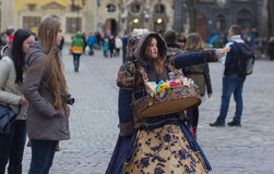 LVIV, UCRÂNIA - 15 de novembro: A menina em um terno bonito vende doces no mercado de Lviv, o 15 de novembro de 2015 em Lviv, Ucr Fotos de Stock