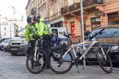 Lviv, Ucrânia 06 11 2018 Dois agentes da polícia em capacetes da bicicleta Patrulha da polícia por bicicletas imagens de stock royalty free