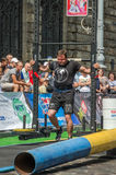 LVIV, UCRÂNIA - EM AGOSTO DE 2017: O atleta forte carrega um balancim enorme pesado nos jogos heroicos no jogo dos homens fortes Imagem de Stock