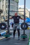 LVIV, UCRÂNIA - EM AGOSTO DE 2017: O atleta forte carrega um balancim enorme pesado nos jogos heroicos no jogo dos homens fortes Fotografia de Stock