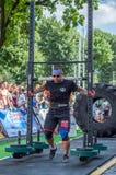 LVIV, UCRÂNIA - EM AGOSTO DE 2017: O atleta forte carrega um balancim enorme pesado nos jogos heroicos no jogo dos homens fortes Fotografia de Stock Royalty Free