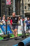 LVIV, UCRÂNIA - EM AGOSTO DE 2017: O atleta forte carrega um balancim enorme pesado nos jogos heroicos no jogo dos homens fortes Fotos de Stock