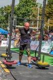 LVIV, UCRÂNIA - EM AGOSTO DE 2017: O atleta forte carrega um balancim enorme pesado nos jogos heroicos no jogo dos homens fortes Foto de Stock