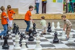 LVIV, UCRÂNIA - EM JUNHO DE 2016: As jovens crianças, os grandmasters futuros jogam em uma xadrez da placa de xadrez que exercita Fotografia de Stock