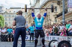 LVIV, UCRÂNIA - EM JUNHO DE 2016: Homem forte do atleta inflado com o corpo atlético que levanta o barbell pesado em uma rua da c Imagens de Stock