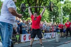LVIV, UCRÂNIA - EM JUNHO DE 2016: Homem forte do atleta inflado com o corpo atlético que levanta o barbell pesado em uma rua da c Fotografia de Stock Royalty Free