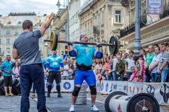 LVIV, UCRÂNIA - EM JUNHO DE 2016: Homem forte do atleta inflado com o corpo atlético que levanta o barbell pesado em uma rua da c Fotos de Stock Royalty Free