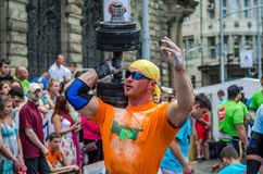 LVIV, UCRÂNIA - EM JUNHO DE 2016: O atleta do homem forte com corpo inflado atlético levanta o peso pesado em uma rua da cidade Foto de Stock