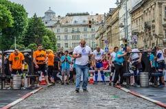 LVIV, UCRÂNIA - EM JUNHO DE 2016: O homem o mais forte no homem forte Vasyl Virastjuk do mundo, com telefone à disposição andando Imagens de Stock Royalty Free