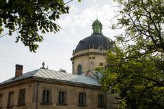 Lviv, Ucrânia: Panorama da rua de Pidvalna com a abóbada da moldação dominiquense da igreja e das árvores Imagem de Stock