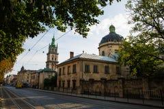 Lviv, Ucrânia: Panorama da rua de Pidvalna com a torre de sino alta da igreja de Dormition e a abóbada da igreja dominiquense Fotografia de Stock Royalty Free