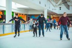 LVIV, UCR?NIA - 3 de fevereiro de 2019: filho de ensino do pai como patinar na pista do esqui fotografia de stock royalty free
