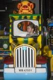 LVIV, UCRÂNIA - EM JANEIRO DE 2018: A menina encantador pequena a criança vai para um passeio em um parque de diversões no carros Imagem de Stock