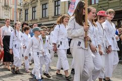 LVIV, UCRÂNIA - EM MAIO DE 2018: Uma coluna das crianças do partido do karaté está andando através do centro da cidade em uma par foto de stock royalty free