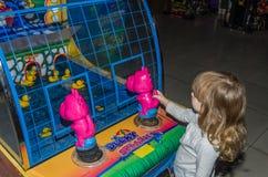 LVIV, UCRÂNIA - EM NOVEMBRO DE 2017: A menina encantador pequena a criança vai para um passeio em um parque de diversões no carro Foto de Stock Royalty Free