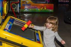 LVIV, UCRÂNIA - EM NOVEMBRO DE 2017: A menina encantador pequena a criança vai para um passeio em um parque de diversões no carro Imagem de Stock