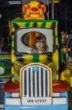 LVIV, UCRÂNIA - EM NOVEMBRO DE 2017: A menina encantador pequena a criança vai para um passeio em um parque de diversões no carro Fotografia de Stock