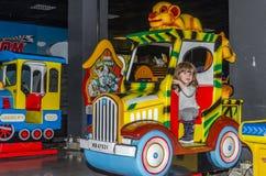 LVIV, UCRÂNIA - EM NOVEMBRO DE 2017: A menina encantador pequena a criança vai para um passeio em um parque de diversões no carro Fotos de Stock Royalty Free