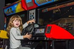LVIV, UCRÂNIA - EM NOVEMBRO DE 2017: A menina encantador pequena a criança vai para um passeio em um parque de diversões no carro Imagens de Stock
