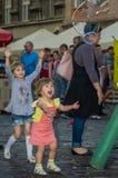 LVIV, UCRANIA - AGOSTO DE 2016: Niños jovenes que cogen burbujas de jabón en la ciudad, jugando, alegre e irradiando las emocione Imágenes de archivo libres de regalías