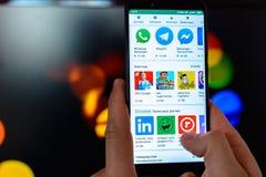 LVIV, UCRANIA - 9 DE MARZO DE 2019: El hombre sostiene el smartphone en su primer de las manos y abre el uso en Google Play encen fotos de archivo libres de regalías