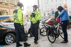 Lviv, Ucrania 06 11 2018 Dos oficiales de policía en cascos de la bicicleta Patrulla de la policía en bicicletas La policía publi imagen de archivo