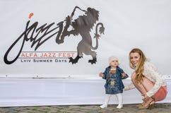 Lviv, Ucrania - junio de 2015: Alfa Jazz Fest 2015 Pequeño bebé con su madre que se sienta al lado de logotipo de los carteles Foto de archivo