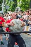 LVIV, UCRANIA - JUNIO DE 2016: El dictador fuerte del culturista levanta una bola de piedra pesada enorme hecha del mármol y la l foto de archivo