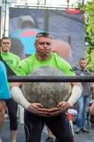 LVIV, UCRANIA - JUNIO DE 2016: El dictador fuerte del culturista levanta una bola de piedra pesada enorme hecha del mármol y la l imágenes de archivo libres de regalías