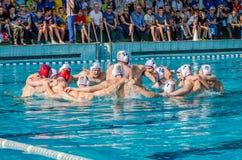 LVIV, UCRANIA - JUNIO DE 2016: Men' adaptan al equipo del water polo de s al juego en la piscina que grita su grito de batal Imagen de archivo libre de regalías