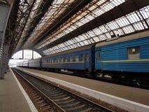 Lviv, Ucrania - oktober 10 2017: El tren de pasajeros se coloca en un ferrocarril perforado debajo de un arco del metal hecho en  Foto de archivo